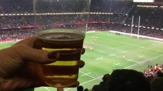A woman holding a beer while watching a Wales rugby match
